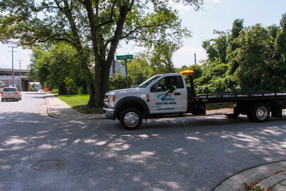 Elite Towing and Transporting truck drives down a residential street towards a broken down car