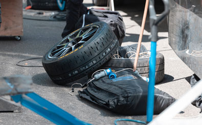 spare tires and automotive mechanic tools lay on roadside